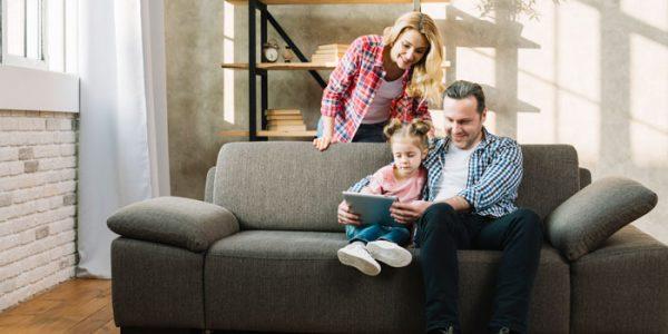 Famiglia seduta su divano che guarda un tablet